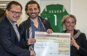 Geschäftsführer Hendrik Schulte-Oechtering (links) nimmt im Namen der Manuel Neuer Kids Foundation den Scheck von Andrea Heiner-Kruckas, Marketing-Direktorin bei der Küppersbusch Hausgeräte GmbH, und dem Künstler Christian Nienhaus in Empfang.