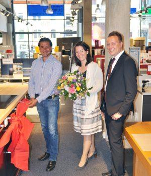 Damaris Landmesser, Head of Trade Marketing Operations bei Electrolux und Key Account Manager Electrolux Jochen Schenkenbach (rechts) überreichen bei der Premiere der ersten AEG Aktiv-Küche im Handel Blumen an André Buddenhagen, Geschäftsführer des gleichnamigen Fachmarkts für Elektrogeräte in Hamburg.