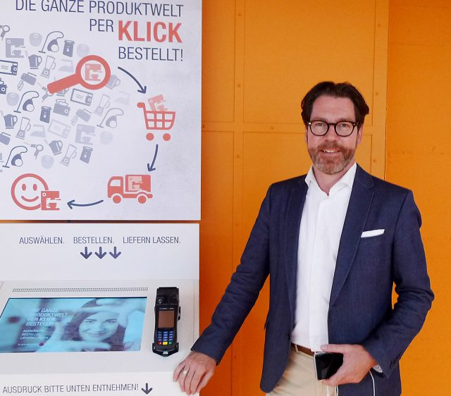 In seiner neuen Funktion bei Springlane besuchte Sven Möller die Messe EK Home und stellte sich infoboard.de vor dem neuen digitalen Kiosk-System zum Foto.